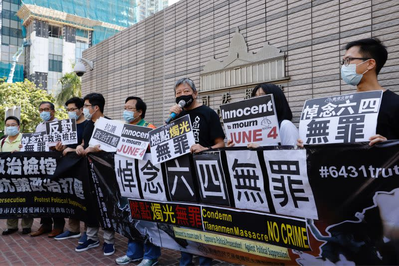 Pro-democracy activists Lee Cheuk-yan holds sign outside West Kowloon Courts in Hong Kong