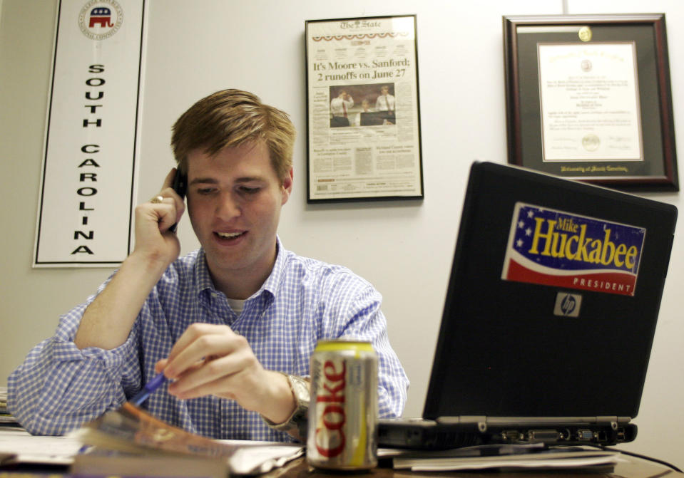 FILE - In this Dec. 28, 2007, file photo, Adam Piper, one of only four full-time staffers for Mike Huckabee's presidential campaign in South Carolina, answers calls and returns emails from the state campaign headquarters in Columbia, S.C. Piper, the executive director of a national group that advocates for Republican attorneys general, resigned from the association five days after the Jan. 6, 2021 violence in Washington. (AP Photo/Brett Flashnick, File)