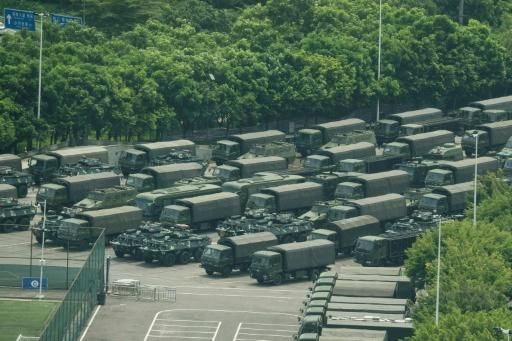 Trucks and armoured personnel carriers are seen outside the Bay stadium in Shenzhen, which borders Hong Kong