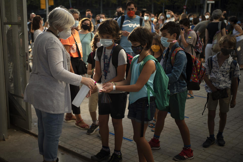 Students wearing face masks to prevent the spread of coronavirus disinfect their hands before entering their school in Barcelona, Spain, Monday, Sept. 14, 2020. Students in Catalonia and Murcia returned to the classrooms for the first time since schools closed due to the coronavirus pandemic. (AP Photo/Emilio Morenatti)
