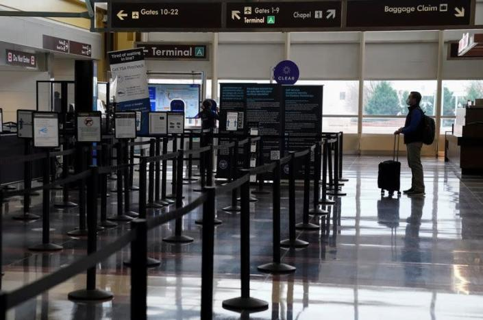 FILE PHOTO: A traveler stands by a security gate at Ronald Reagan Washington National Airport in Arlington, Virginia