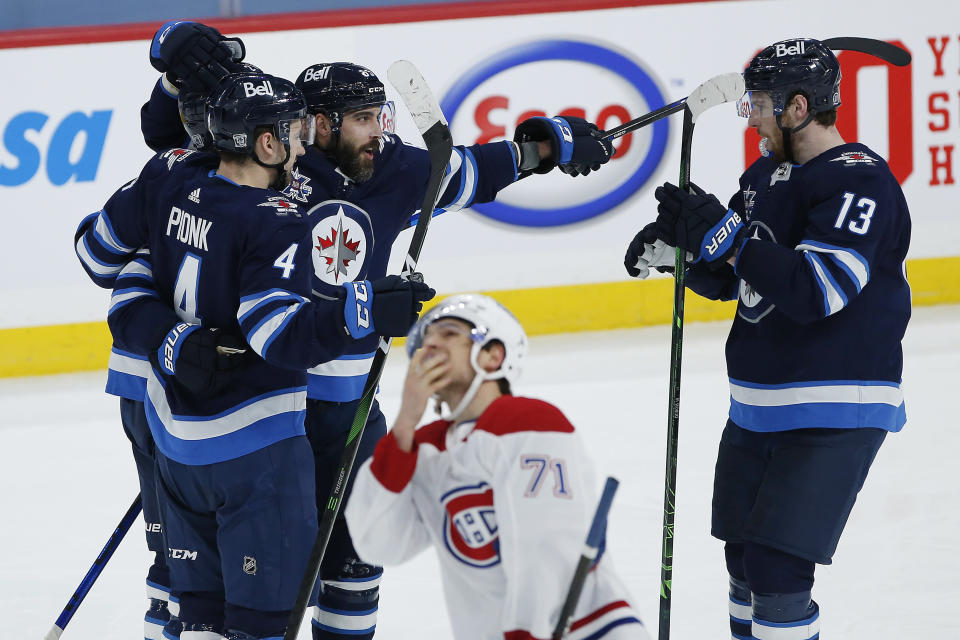 Winnipeg Jets' Neal Pionk (4), Nikolaj Ehlers (27), Mathieu Perreault (85) and Pierre-Luc Dubois (13) celebrate Ehlers' goal as Montreal Canadiens' Jake Evans (71) skates past during the second period of an NHL hockey game Saturday, Feb. 27, 2021, in Winnipeg, Manitoba. (John Woods/The Canadian Press via AP)