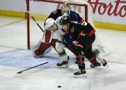 Vancouver Canucks left wing Nils Hoglander (36) loses his stick as he battles with Ottawa Senators defenceman Mike Reilly in front of goaltender Joey Daccord during the second period of an NHL hockey game in Ottawa, Ontario, Monday, March 15, 2021. (Adrian Wyld/The Canadian Press via AP)