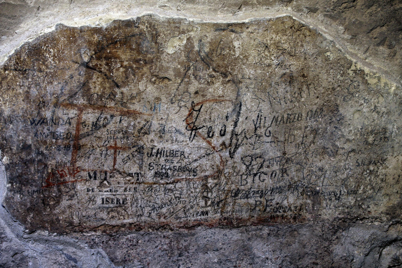 An ancient graffiti, in background red, covered by tourist's graffiti, is seen inside a gallery of Rome's Colosseum, Friday, Jan. 18, 2013. A long-delayed restoration of the Colosseum's only intact internal passageway has yielded ancient traces of red, black and blue frescoes — as well as graffiti and drawings of phallic symbols — indicating that the arena where gladiators fought was far more colorful than previously thought. Officials unveiled the discoveries Friday and said the passageway would be open to the public starting this summer, after the €80,000 ($100,000) restoration is completed. The frescoes were hidden under decades of calcified rock and grime, and were revealed after the surfaces were cleaned. The traces confirmed that while the Colosseum today is a fairly monochrome gray travertine rock, red brick and bits of moss-covered marble, in its day its interior halls were a rich and expensive Technicolor. (AP Photo/Gregorio Borgia)