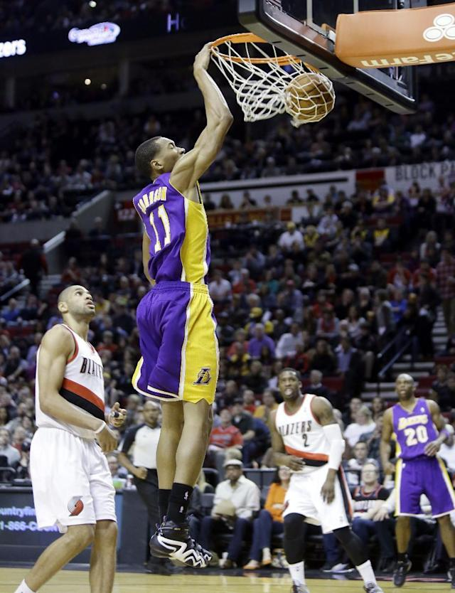 Los Angeles Lakers forward Wesley Johnson, right, scores on a fast break against Portland Trail Blazers forward Nicolas Batum, of France, during the first half of an NBA basketball game in Portland, Ore., Monday, March 3, 2014. (AP Photo/Don Ryan)