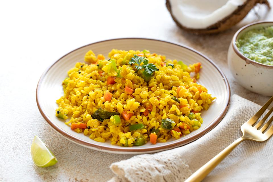 Indian cuisine Indian food. Indian cuisine. Poha or flattened rice traditional Western Indian breakfast with coconut chutney sauce curry leaves. national authentic vegetarian Asian food