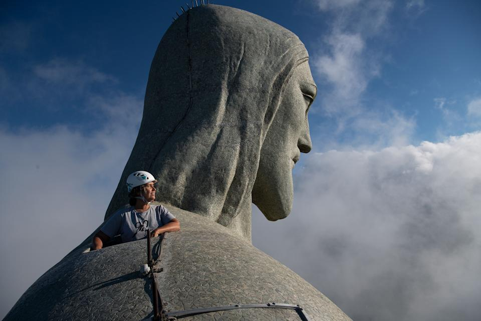 TOPSHOT - Architect Cristina Ventura, who is in charge of the Christ the Redeemer statue restoration, looks out from the top of the Christ the Redeemer statue in Rio de Janeiro, Brazil, on March 24, 2021. - Christ the Redeemer is celebrating its 90th anniversary in October 2021 and is receiving restoration work to ensure that it looks its best for the public and visiting tourists. (Photo by CARL DE SOUZA / AFP) / The erroneous mention[s] appearing in the metadata of this photo by CARL DE SOUZA has been modified in AFP systems in the following manner: [2021] instead of [2020]. Please immediately remove the erroneous mention[s] from all your online services and delete it (them) from your servers. If you have been authorized by AFP to distribute it (them) to third parties, please ensure that the same actions are carried out by them. Failure to promptly comply with these instructions will entail liability on your part for any continued or post notification usage. Therefore we thank you very much for all your attention and prompt action. We are sorry for the inconvenience this notification may cause and remain at your disposal for any further information you may require. (Photo by CARL DE SOUZA/AFP via Getty Images)