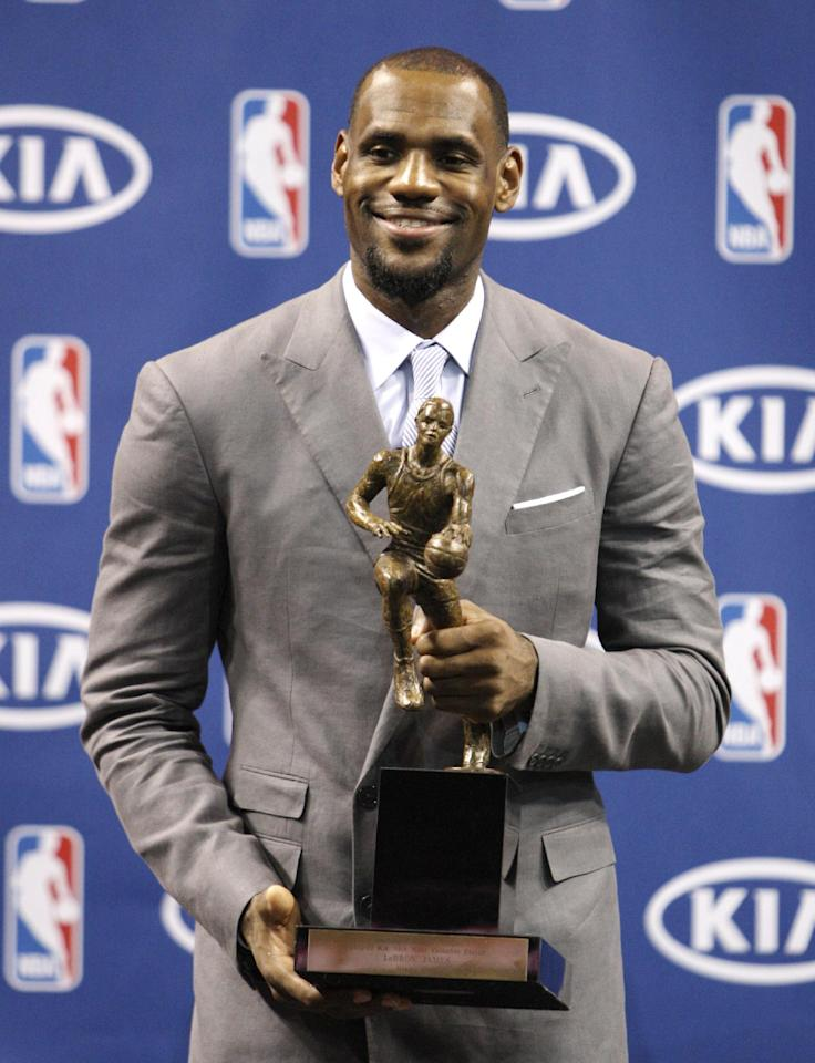 "LeBron James poses after having accepted the NBA MVP trophy, Saturday, May 12, 2012 in Miami. Calling the honor ""overwhelming"" but pointing to a ""bigger goal,"" James on Saturday became the eighth player in NBA history to win the MVP award three times. (AP Photo/Wilfredo Lee)"