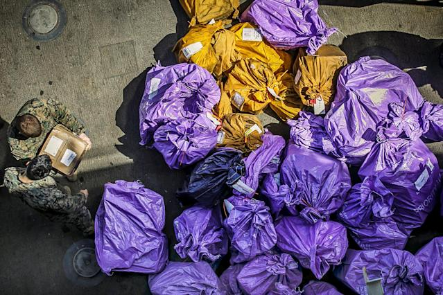 U.S. Marines sort through mail delivered aboard the U.S. Navy Harpers Ferry-class dock landing ship USS Oak Hill in the Aegean Sea, March 24, 2018. Picture taken March 24, 2018. U.S. Marine Corps/Staff Sgt. Dengrier M. Baez/Handout via REUTERS. ATTENTION EDITORS - THIS IMAGE WAS PROVIDED BY A THIRD PARTY