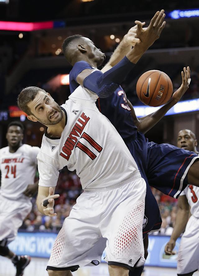 Louisville forward Luke Hancock (11) battles Connecticut center Amida Brimah (35) for a rebound during the first half of an NCAA college basketball game in the finals of the American Athletic Conference men's tournament Saturday, March 15, 2014, in Memphis, Tenn. (AP Photo/Mark Humphrey)