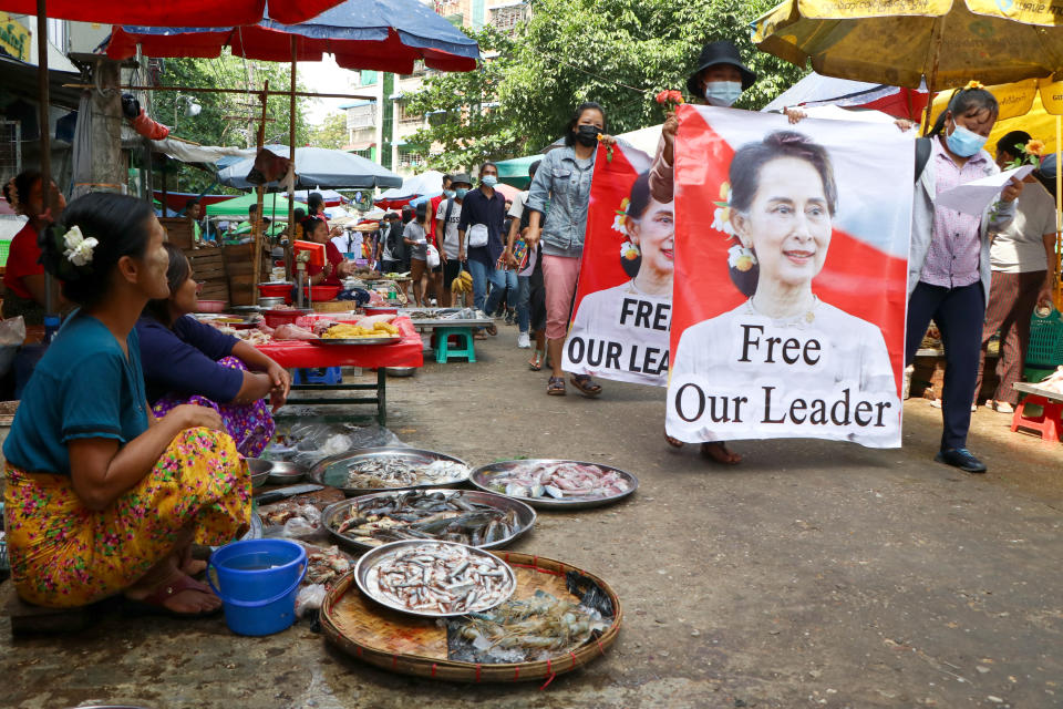 Anti-coup protesters walk through a market with images of ousted Myanmar leader Aung San Suu Kyi at Kamayut township in Yangon, Myanmar Thursday, April 8, 2021. They walked through the markets and streets of Kamayut township with slogans to show their disaffection for military coup. (AP Photo)