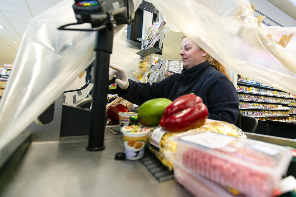 20 March 2020, Schleswig-Holstein, Langballig: Cashier Bianca Krüger scans goods in an Edeka supermarket in the Schleswig-Flensburg district under a plastic foil. With this protective measure, the employees want to protect themselves from possible infection by the customers. Photo: Frank Molter/dpa (Photo by Frank Molter/picture alliance via Getty Images)