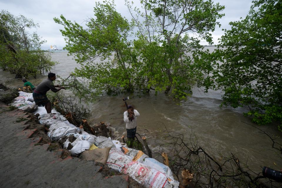 "Villagers reinforce an embankment with sacks of soil ahead of the expected landfall of cyclone Amphan, in Dacope on May 20, 2020. - Several million people were taking shelter and praying for the best on Wednesday as the Bay of Bengal's fiercest cyclone in decades roared towards Bangladesh and eastern India, with forecasts of a potentially devastating and deadly storm surge. Authorities have scrambled to evacuate low lying areas in the path of Amphan, which is only the second ""super cyclone"" to form in the northeastern Indian Ocean since records began. (Photo by Munir Uz zaman / AFP) (Photo by MUNIR UZ ZAMAN/AFP via Getty Images)"