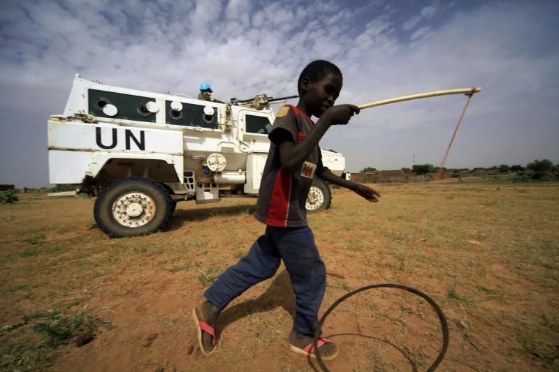 File picture of a boy playing in front of UNAMID peacekeeper standing guard near women development program centre in North Darfur