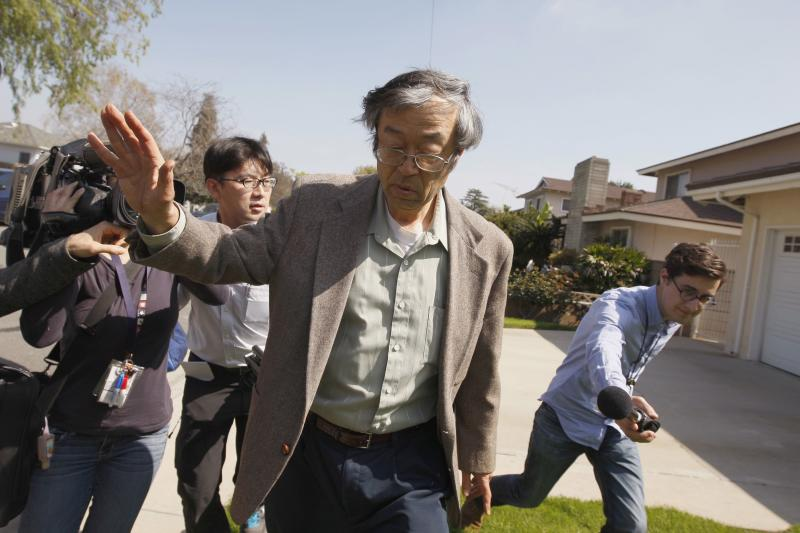 Satoshi Nakamoto is surrounded by reporters as he leaves his home in Temple City, California