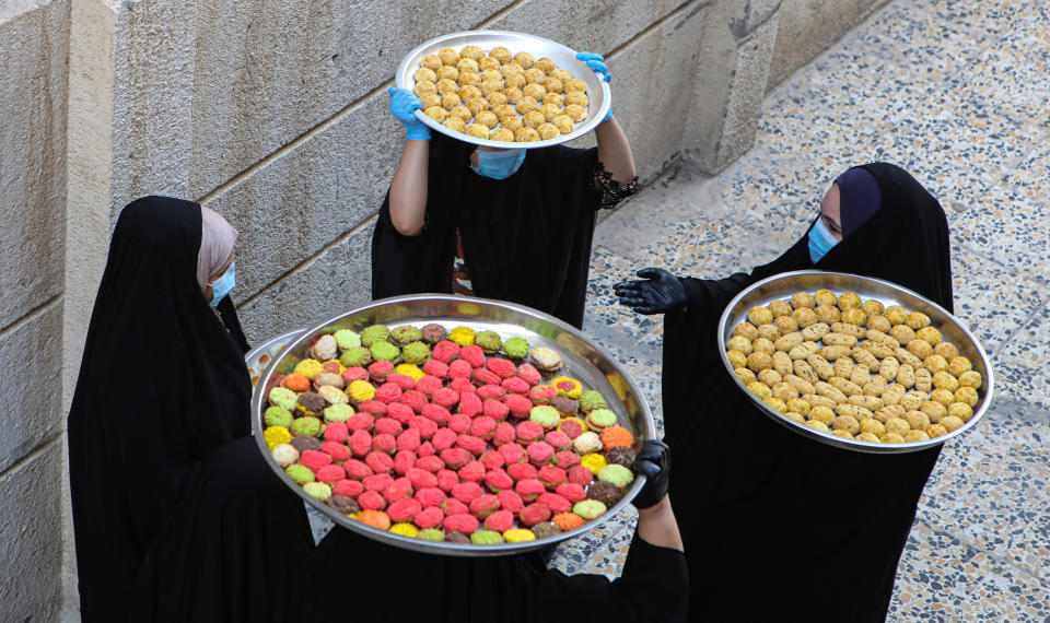 Iraqi women carry cookies for the upcoming Muslim Eid al- Fitr celebrations, that marks the end of the Muslim holy fasting month of Ramadan, in Basra, Iraq, Friday, May 22, 2020. (AP Photo/Nabil al-Jurani)