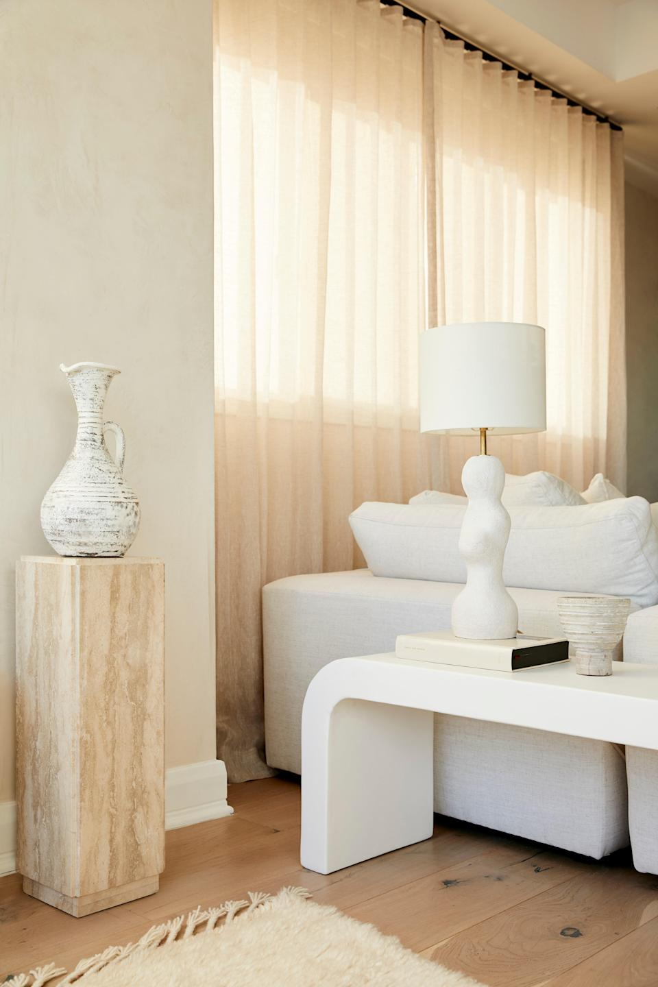 """""""It's really a collaborative effort,"""" says Hewitt of working with Garcia. Inspired by chic European decor, the duo set out to find a healthy balance of luxury and warmth. Here, a white plaster bench resides next to a weathered marble side table."""