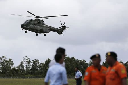Search and rescue team members stand by as a helicopter prepares to land, during search operations for passengers onboard AirAsia flight QZ8501, at Iskandar airbase in Pangkalan Bun district, Indonesia, December 31, 2014. REUTERS/Beawiharta