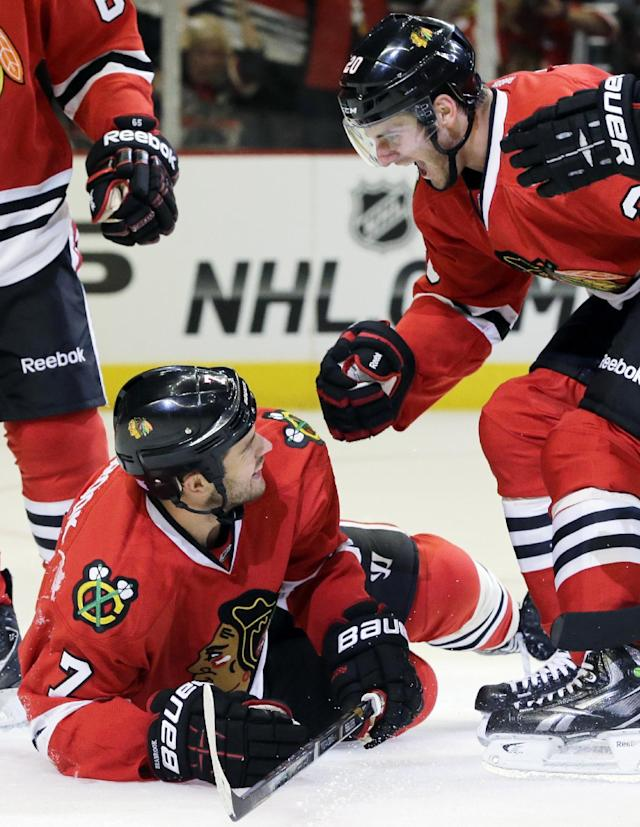 Chicago Blackhawks' Brent Seabrook (7) celebrates with Brandon Saad (20) after scoring a goal during the second period of an NHL hockey game against the Washington Capitals, Tuesday, Oct. 1, 2013, in Chicago. (AP Photo/Nam Y. Huh)