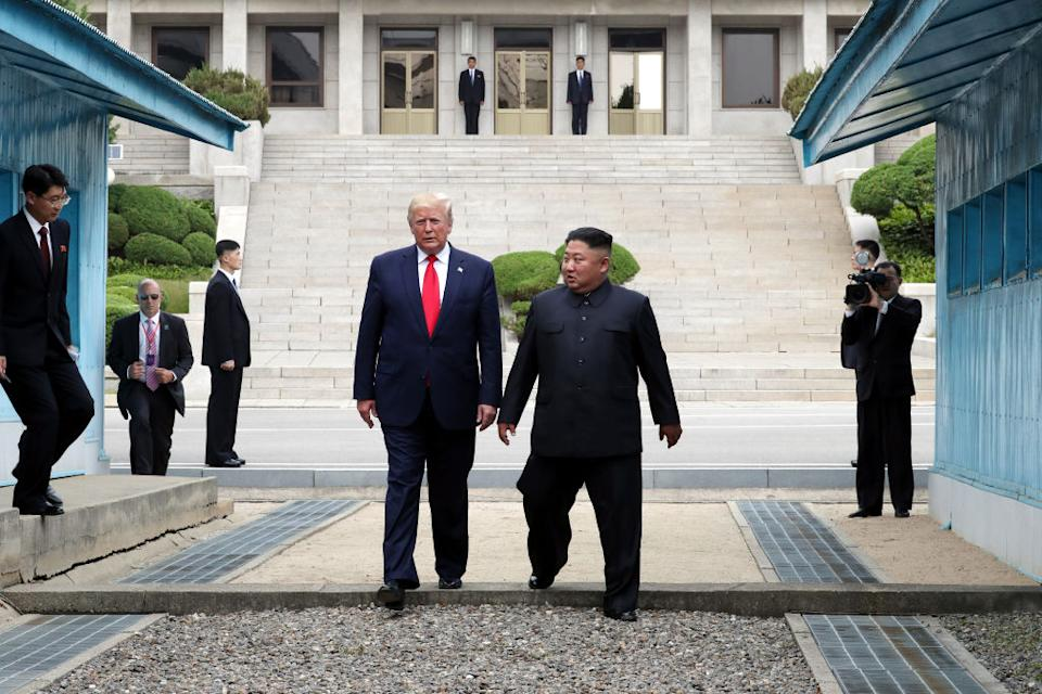 Donald Trump and Kim Jong-un stand next to each other during political talks.