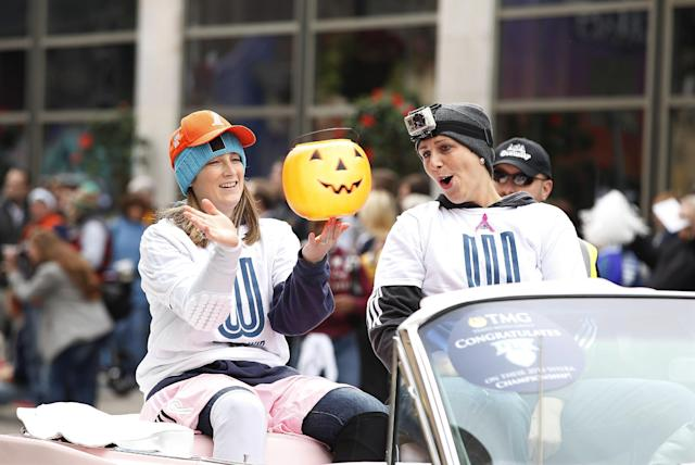 Minnesota Lynx guard Lindsay Whalen, left, spins a plastic pumpkin on her finger, as teammate forward Janel McCarville, right, cheers her on during the celebratory parade for their WNBA Championship title, Monday, Oct. 14, 2013, in Minneapolis. (AP Photo/Stacy Bengs)