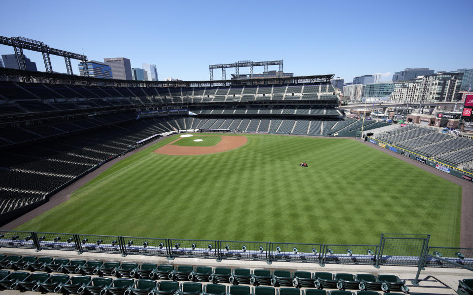 A lone member of the field crew mows the lawn in Coors Field.