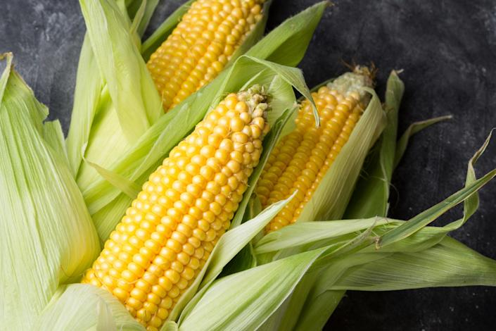 Three fresh ears of corn in a stack, half shucked