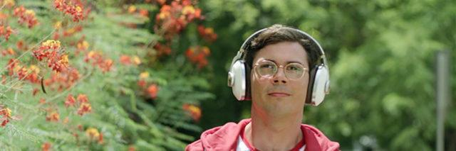 """Ryan, the main character in """"Special"""" wearing headphones outside."""