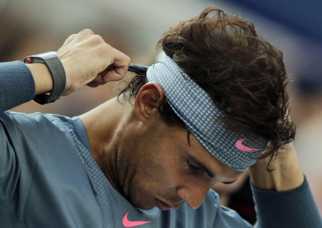 Rafael Nadal, of Spain, re-ties his headband after a break between games against Novak Djokovic, of Serbia, during the men's singles final of the 2013 U.S. Open tennis tournament, Monday, Sept. 9, 2013, in New York. (AP Photo/Charles Krupa)