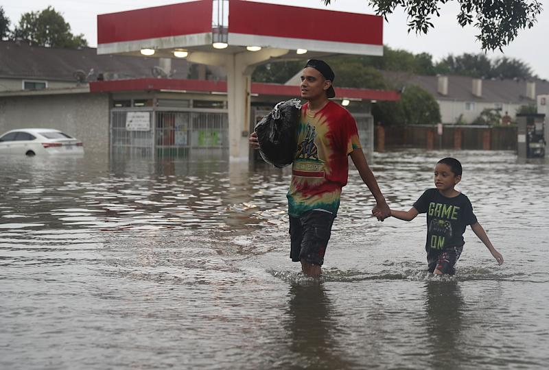 People walk down a flooded Houston street as they evacuate their homes Sunday after Hurricane Harvey hit. (Joe Raedle via Getty Images)