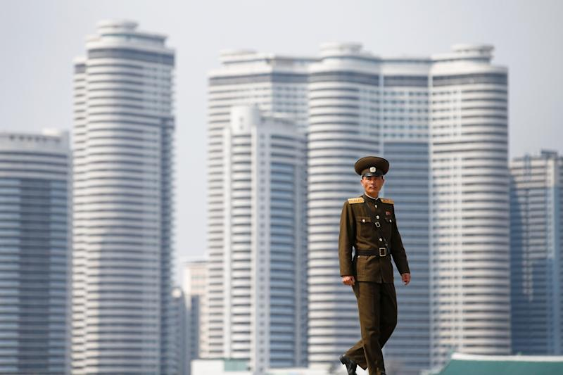 A soldier walks on the bank of the river in central Pyongyang