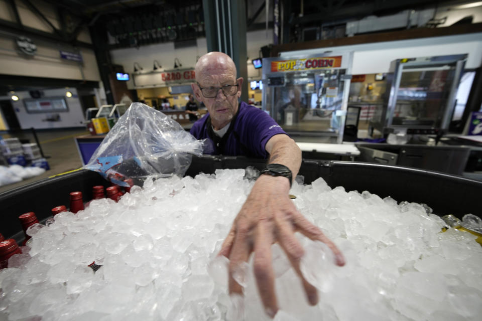 As temperatures soar into the triple digits for the third straight day, vendor James Oehlerking spreads ice over a tub of bottled beer to prepare the drinks for sale on the main concourse of Coors Field before the first inning of a baseball game Thursday, June 17, 2021, in Denver. (AP Photo/David Zalubowski)