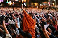 A Buddhist monk gives the three-finger salute with pro-democracy protesters during a rally at Asok in Bangkok