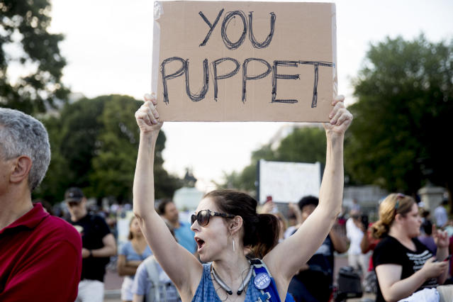 "A woman holds a sign that reads ""You Puppet"" during a protest outside the White House on Tuesday. (Photo: Andrew Harnik/AP)"