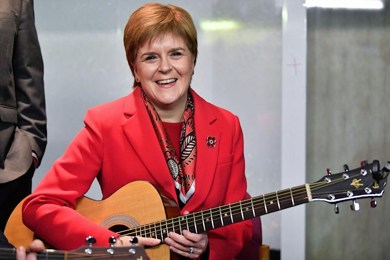 """DALKEITH, SCOTLAND - NOVEMBER 05: First Minister Nicola Sturgeon holds a guitar as she visits Dalkeith Community Hub with Owen Thompson, SNP election candidate for Midlothian on November 5, 2019 in Dalkeith, Scotland. Nicola Sturgeon said """"Brexit is far from a done deal even if Boris Johnson was to get his deal passed, that would only be the beginning – not the end – of trade talks with the EU. (Photo by Jeff J Mitchell/Getty Images)"""