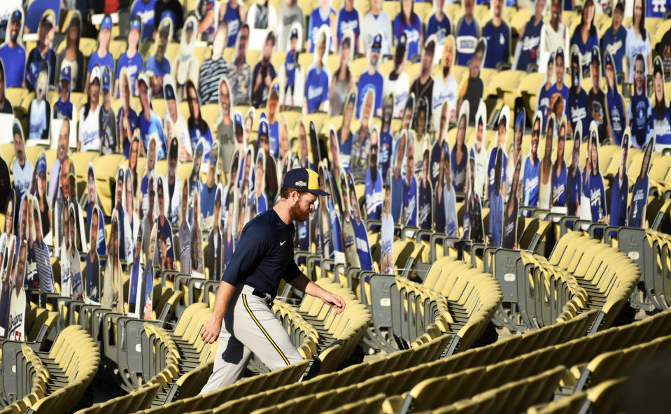 Milwaukee Brewers pitcher Brandon Woodruff walks past fan cut-outs in the stands before a workout, Tuesday, Sept. 29, 2020, at Dodger Stadium in Los Angeles, ahead of Wednesday's Game 1 of a National League wild-card baseball series against the Los Angeles Dodgers. (AP Photo/Chris Pizzello)