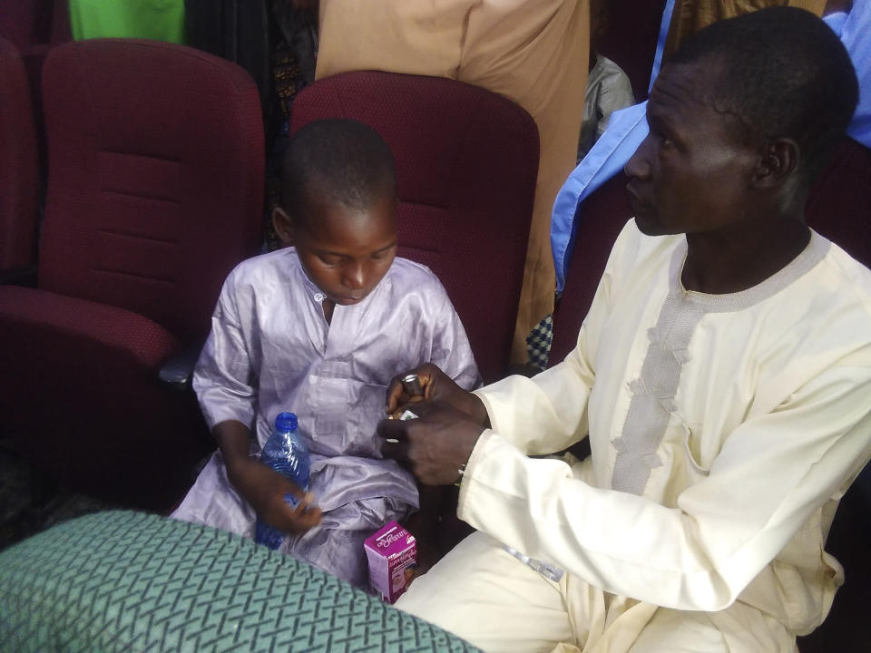 A freed student of Salihu Tanko Islamic School, reunited with his father in Minna, Nigeria Friday, Aug 27, 2021. A school official in northern Nigeria says gunmen have released some of the more than 100 children who had been abducted back in May. The kidnapping victims from the Salihu Tanko Islamic School in Niger state had included children as young as 5 years old. (AP Photo)