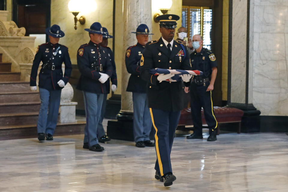 A member of the Mississippi National Guard carries a folded decommissioned Mississippi state flag in the Capitol where it was handed over to state officials during a retirement ceremony after it was first flown over the legislative chambers one final time in Jackson, Miss., Wednesday, July 1, 2020. The banner was the last state flag with the Confederate battle emblem on it. (AP Photo/Rogelio V. Solis)