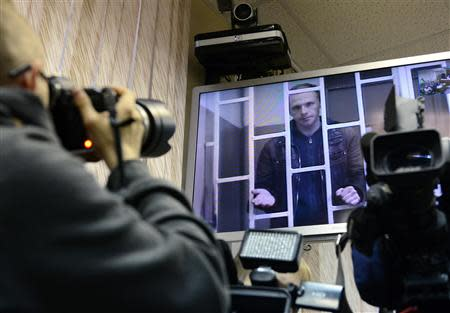 Photographer Denis Sinyakov, one of the 30 people detained after a Greenpeace protest at the Prirazlomnaya platform who is currently held at a pretrial detention centre, is seen on a screen installed inside a court building during a court session in Murmansk, October 8, 2013. REUTERS/Stringer