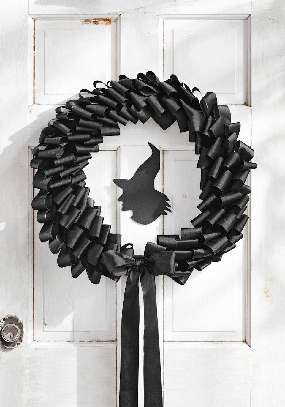 <p>We're spooked in the best way by this black wreath. A witch silhouette in the middle keeps it perfectly on-theme.</p><p><strong>Make the Wreath: </strong>Cut 150 6-inch-long strips of 2-inch-wide black grosgrain ribbon. Fold the strips in half and attach them to a 16-inch foam wreath form with straight pins, layering them on top of each other to create a ruffle effect. Cut out a silhouette of a witch from black kraft paper. Attach it to the center of a 16-inch round clear piece of acrylic with double-sided tape. Hot-glue the edges of the acrylic round to the back of the wreath form. Finish with a bow with long tails. </p>