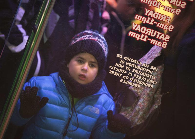 """A boy looks in the window as he lines up outside a Toys""""R""""Us store in Times Square before their Black Friday Sale in New York"""