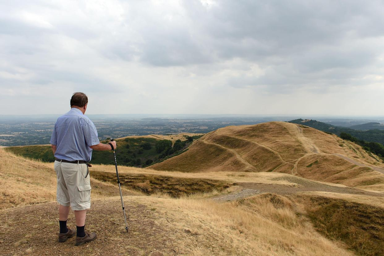A walker looks out from British Camp in the Malvern Hills in Worcestershire during this year's heatwave. (PA Images)