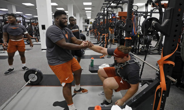 Texas Longhorns' Keondre Coburn (left) helps teammate Zach Shackelford up during works out Wednesday Sept. 4, 2019 in Austin, Tx. ( Photo by Edward A. Ornelas )