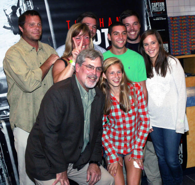 """Captain Richard Phillips, the real-life ship captain being played by Tom Hanks in the docudrama """"Captain Phillips,"""" front left, poses with friends before a screening of """"Captain Phillips,"""" on Tuesday, Oct. 1, 2013 in Williston, Vt. The film was adapted from the captain's memoir about the 2009 hijacking of his vessel by Somali pirates. Phillips spent five days as a hostage of the pirates on a lifeboat, where he was beaten, tied up and threatened before he was rescued days later by U.S. Navy SEALs. (AP Photo/Toby Talbot)"""