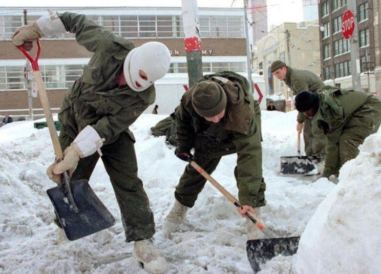 TORONTO, CANADA: Soldiers from Royal Regiment of Canada shovel snow 15 January in downtown Toronto, Canada's largest city and financial capital. Heavy snow and frigid temperatures have continued to grip eastern and central Canada, forcing authorities to close schools and offices and call out the military. AFP PHOTO/Thomas CHENG (Photo credit should read THOMAS CHENG/AFP/Getty Images)