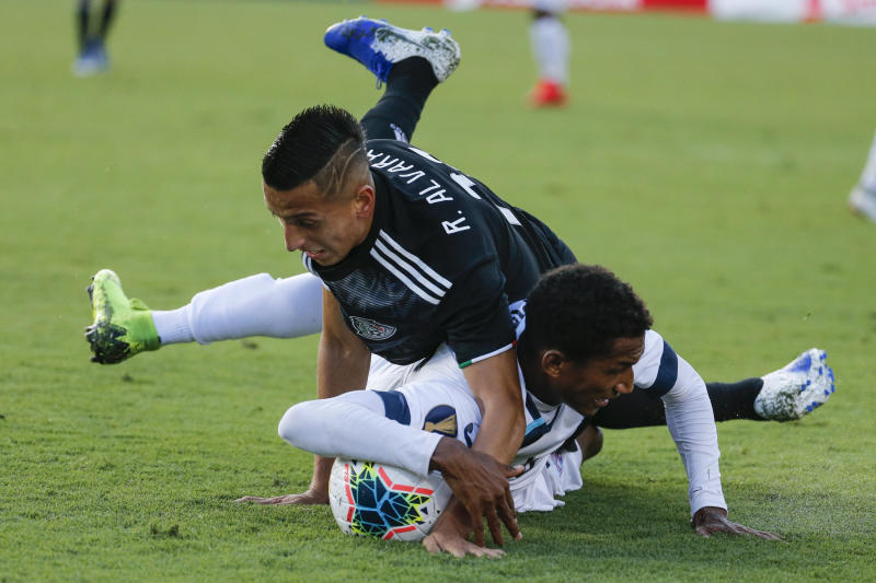 Mexico midfielder Roberto Alvarado, top, and Cuba defender Yosel Piedra collide above the ball during the first half of a CONCACAF Gold Cup soccer match in Pasadena, Calif., Saturday, June 15, 2019. (AP Photo/Ringo H.W. Chiu)