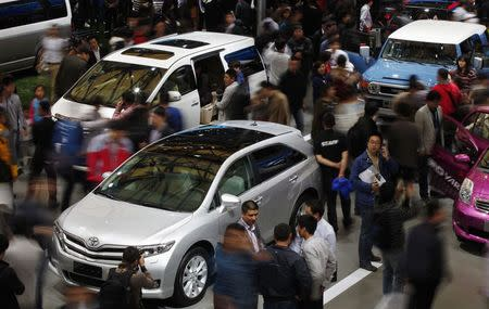 People look at Toyota cars during the 15th Shanghai International Automobile Industry Exhibition in this April 21, 2013 file photo. REUTERS/Carlos Barria
