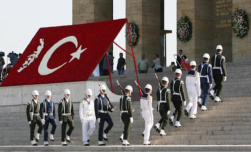 FILE - In this May 19, 2008 file photo, a Turkish military guard of honour pass by a map of Turkey and a portrait of Mustafa Kemal Ataturk, both made of carnations at his mausoleum on the Youth Day in Ankara, Turkey. Ataturk, Turkey's independence war hero, national founder in a time of crisis, imposer of secular ideas on a mostly Muslim population and a hallowed presence long after his death. The cult of Ataturk, once a staple of Turkish state ideology, is slowly, sometimes imperceptibly, being diluted, replaced in part by the Ottoman imperial era as inspiration for a government with its own set of ideas about modernity, morality and regional stature.(AP Photo/Burhan Ozbilici, File)
