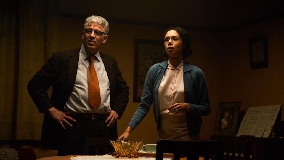 a woman depicting Rosa Parks stands beside a man wearing a dark suit in a dimly lit room