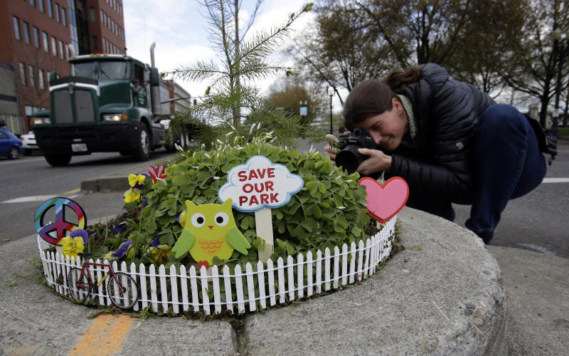 Allison Wildman crouches low to get a photo of Mill Ends Park in Portland, Ore., Thursday, April 11, 2013.  Tiny battle lines are being drawn in a whimsical British-American dispute over which country has the world's smallest park. Two feet in diameter, Portland's Mill Ends Park holds the title of world's smallest park in the Guinness Book of World Records. But a rival has emerged--Prince's Park, more than 5,000 miles away in the English town of Burntwood  which holds the record for smallest park in the United Kingdom.(AP Photo/Don Ryan)